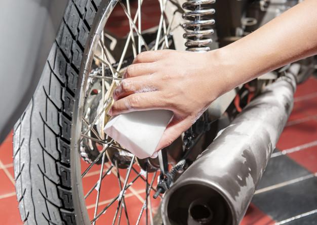 Moto sendo lavada com esponja branca.